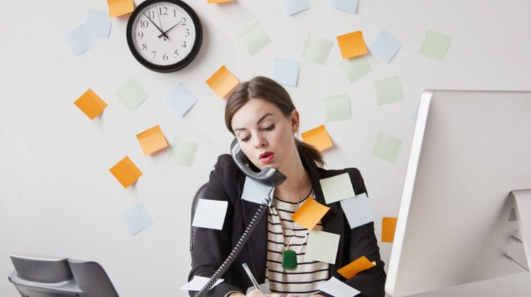 Busy season: Studio shot of young woman working in office covered with adhesive notes